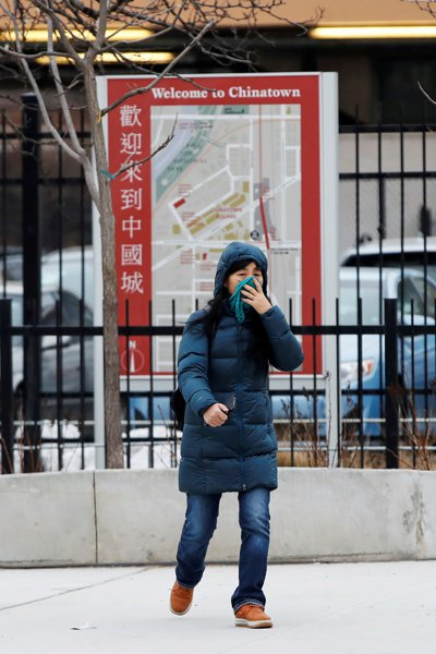 一名女子用手帕遮臉,走進美國芝加哥中國城。 (路透)