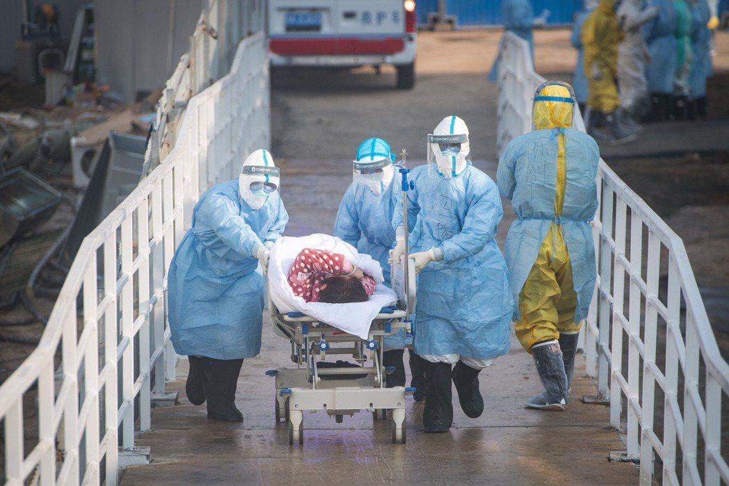2月4日,醫療人員協助確診患者轉入武漢火神山醫院。 圖/新華社