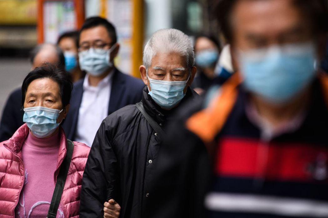 武漢肺炎疫情擴散,路上民眾戴起口罩自保。 圖/法新社