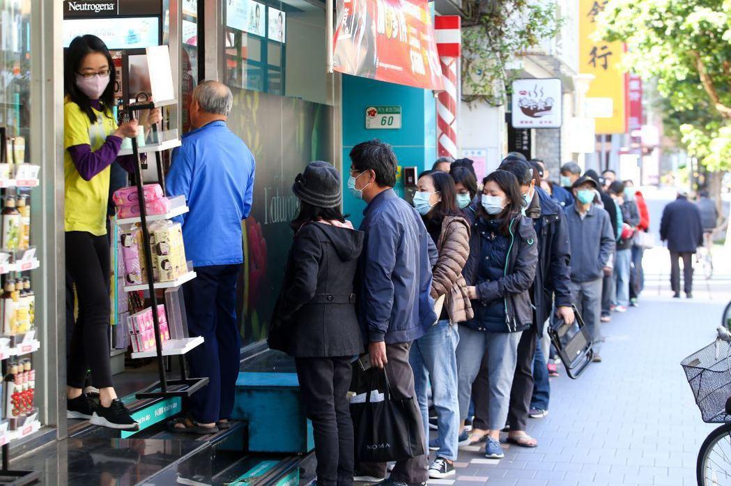 武漢肺炎疫情擴散,民眾於藥妝店前排隊購買口罩防疫。 圖/聯合報系資料照