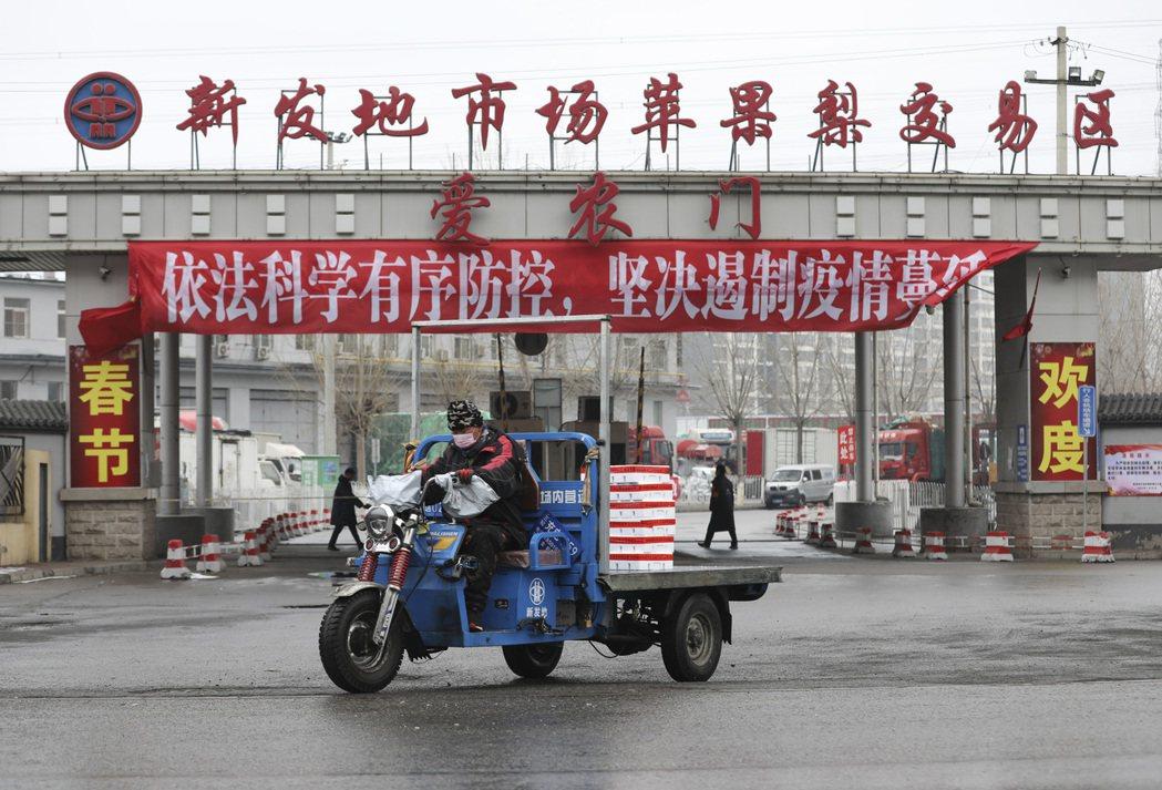 北京市內一位工作人員戴著口罩在運輸農產品。 圖/中新社