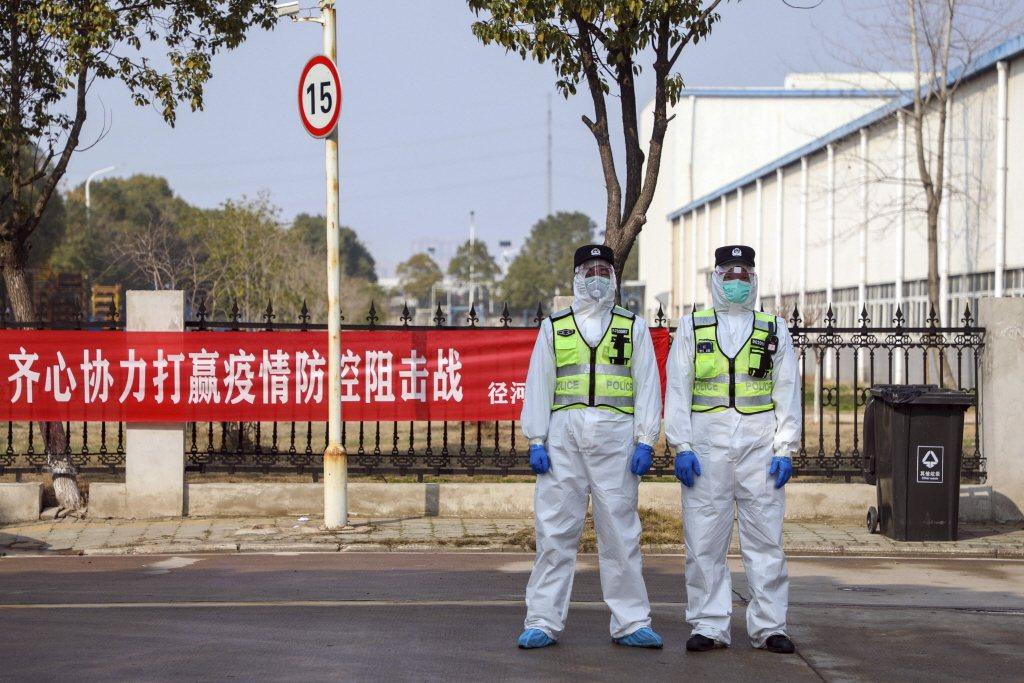 武漢警察著防護衣於隔離點外站崗。 圖/美聯社