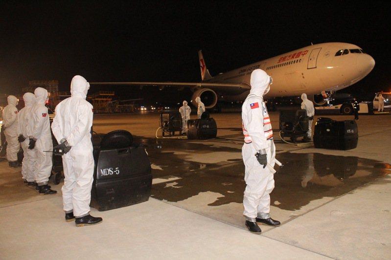 防護衣上有國旗的33化學兵群,昨晚前往桃園國際機場協助防疫消毒作業,圖右為中國東方航空專機。圖/中華民國陸軍臉書粉絲專頁