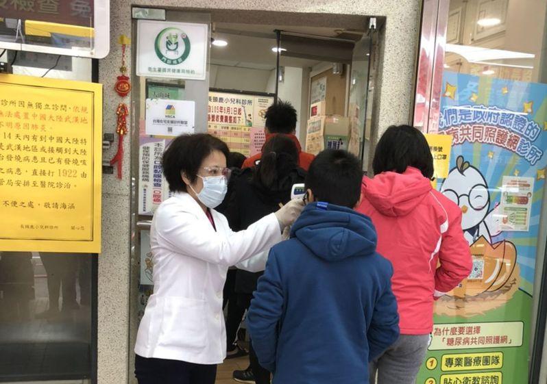 武漢肺炎增溫,台中市很多診所反映,第一線醫護人員每天接觸逾百名病患,用的是耳溫槍,很擔心遭感染,圖為診所人員以額溫槍為進診所民眾量額溫。記者趙容萱/攝影