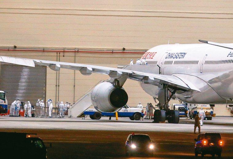圖為接回首批武漢台商的包機三日深夜抵達桃園機場,工作人員陸續登上飛機。 圖/聯合...