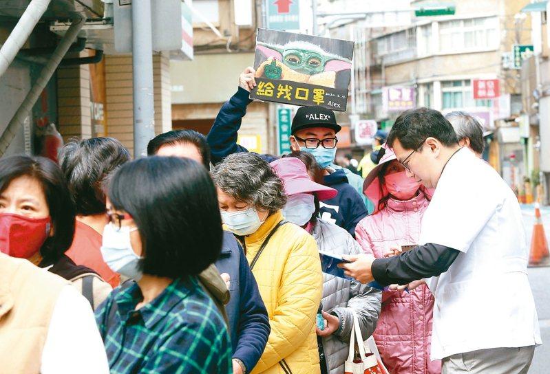 藥師在開賣前先一一核對購買資格,一位民眾拿著寫「給我口罩」的看板排隊。 記者邱德祥/攝影