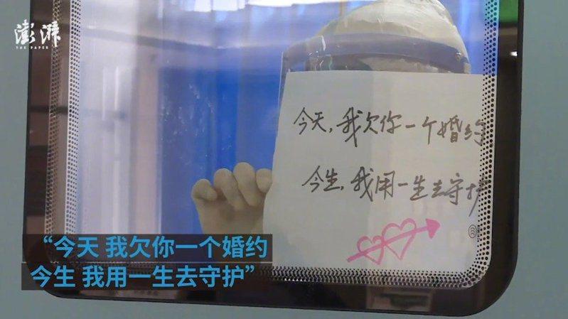 四川成都醫生張仕華透過隔離區玻璃向未婚妻表達愛意與歉意。圖/澎湃新聞