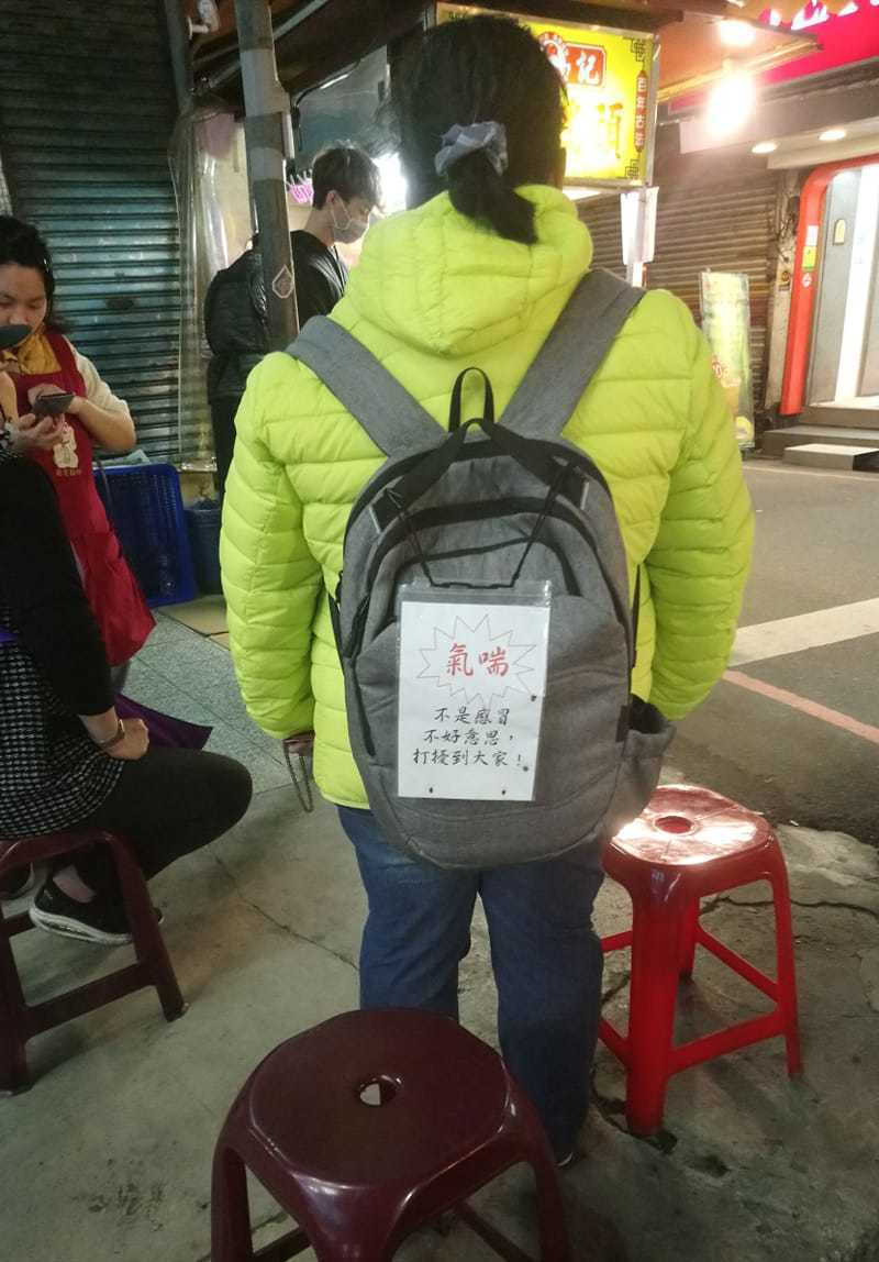 女子有氣喘疾病,但怕引起民眾恐慌,所以在背後掛上告示牌。圖擷自臉書社團「爆怨公社」