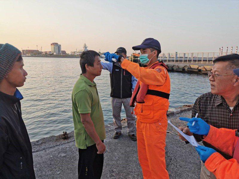 高雄加強海上防疫,海巡署人員對入港船員量測額溫。圖/高市海洋局提供