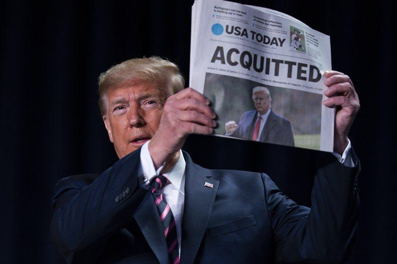 美國總統川普6日出席全國祈禱早餐會時,秀出報紙斗大的頭條標題「無罪」。(美聯社)