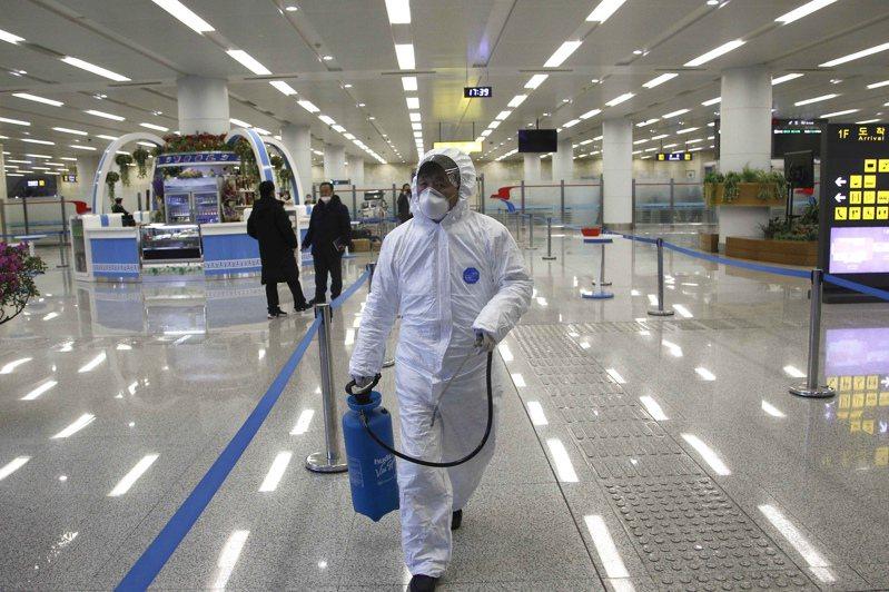 穿戴防護衣的北韓人員1日在平壤機場內消毒。 (美聯社)