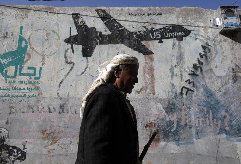 美國總統川普6日宣布,美國在葉門的擊斃阿拉伯半島凱達組織領導人瑞米。圖為一名葉門民眾走過美國無人機的塗鴉之前。歐新社