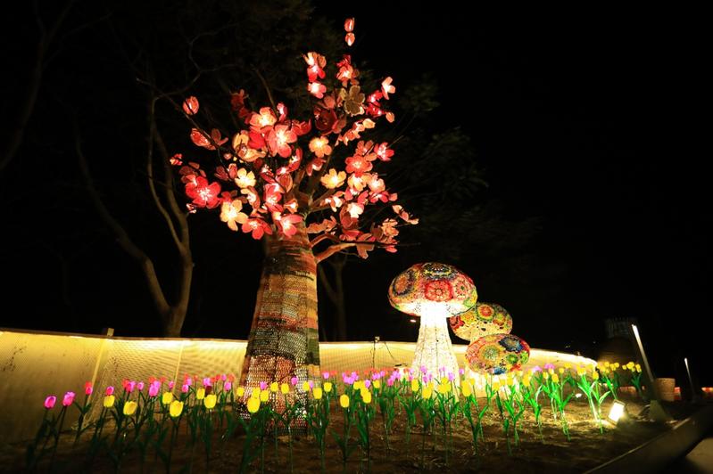 藝術家楊海茜率領30多位客家婦女鉤織高手,首次挑戰有別於以往平面或幾何編織法的「立體鉤織法」,花費2個月編成上百朵櫻花,創作出5公尺高的山櫻花樹。圖/台中市政府提供