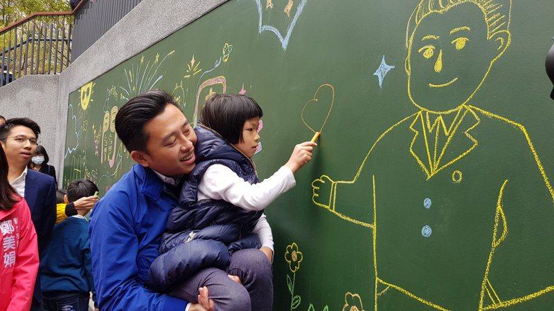 新竹市關新公園整建工程設置塗鴉牆,市長林智堅抱起小朋友在牆上塗鴉。記者黃瑞典/攝影