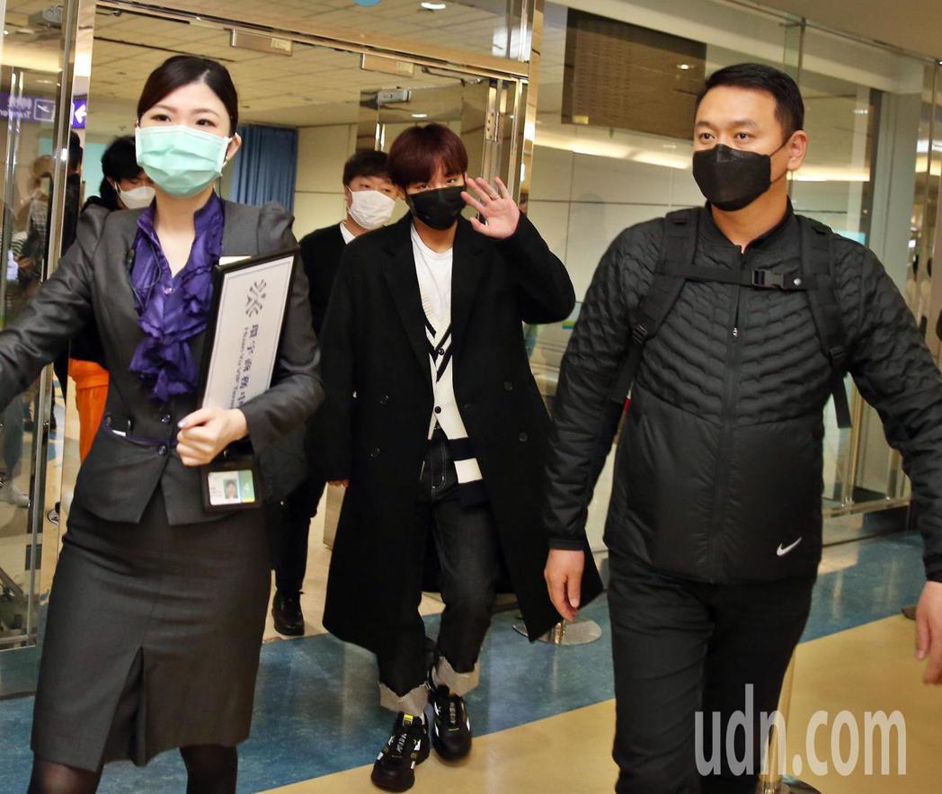 韓團「Wanna One」前成員朴志訓(中)下午抵台,他戴著黑色口罩,向粉絲揮手...