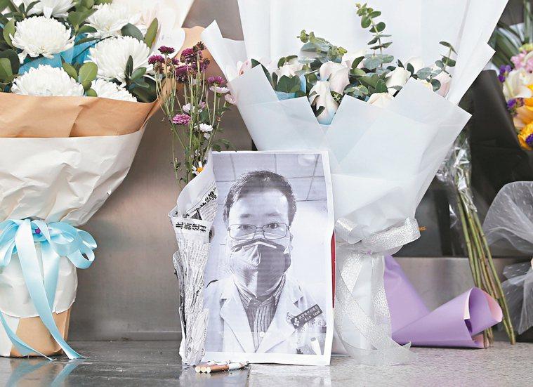 武漢民眾在武漢市中心醫院附近一處臨時處所放置李文亮的遺照悼念他。 歐新社
