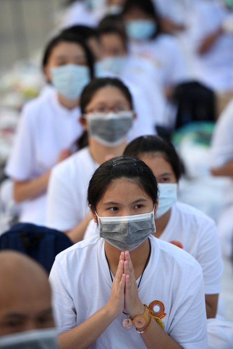 泰國民眾8日戴口罩,在曼谷近郊法身寺祈禱。(路透)