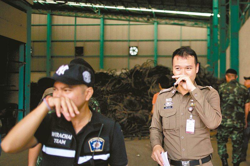 泰國警察臨檢曼谷市郊的電子廢棄物處理廠,因現場臭氣濃烈而以手掩鼻。 美聯社