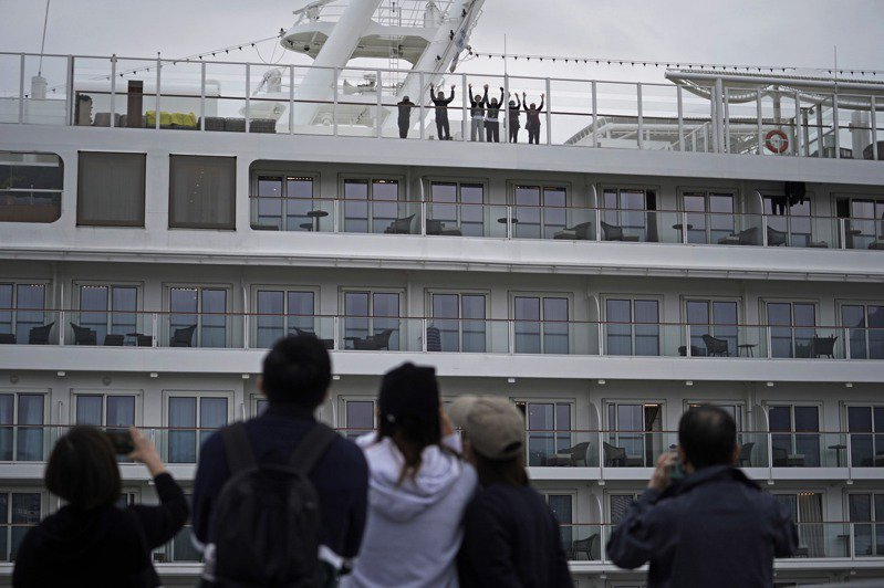 「世界夢號」郵輪仍停泊在啟德郵輪碼頭,船上乘客8日向岸上的家人揮手。  美聯社