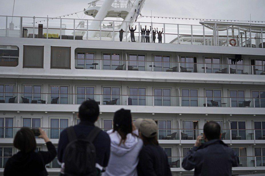 「世界夢號」郵輪停泊香港5天,接受2019新型冠狀病毒肺炎的檢疫程序,約1800名船員均呈陰性反應,終於讓船上所有旅客都可下船。圖為船上乘客8日向岸上的家人揮手。  美聯社
