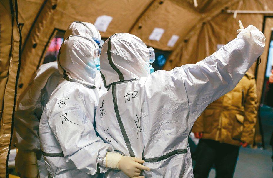 大陸昨天有89人因感染武漢新冠肺炎死亡,創單日紀錄;圖為準備進入武漢方艙醫院的醫護人員防護衣上寫著「武漢加油」字樣。 中新社
