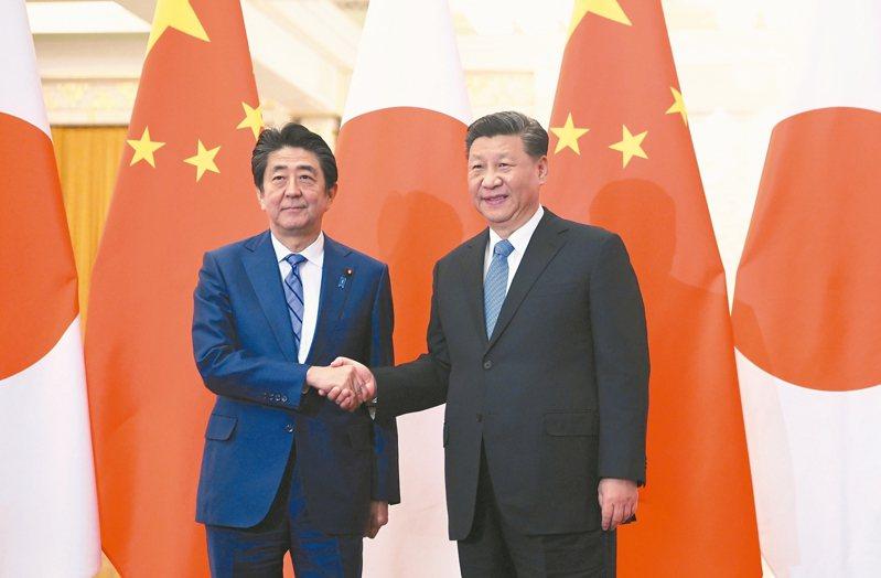 中國大陸國家主席習近平(右)去年12月底在北京會見日本首相安倍晉三(左)。 美聯社