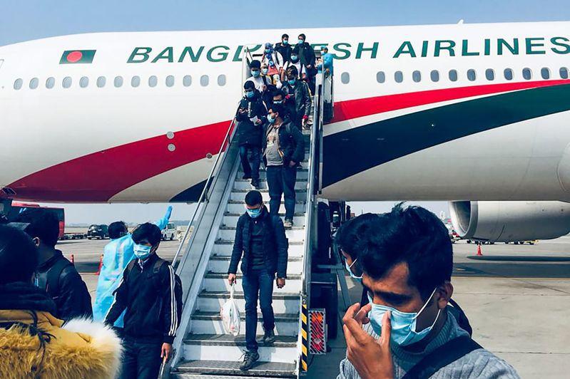 圖為孟國撤僑包機1日抵達沙拉賈拉勒國際機場後的僑民下機畫面。法新社