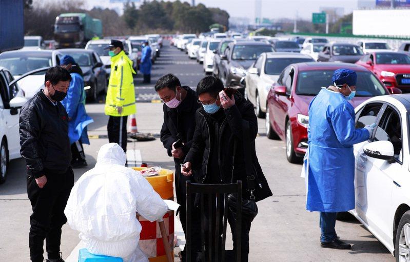 為加強疫情防控,在滬渝高速入滬通道省界公安檢查站,防疫人員「逢車必檢,逢人必查」,確定車的來源,為每一位進入上海者測量體溫。 中新社