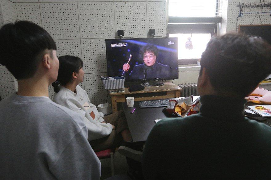 南韓韓國影友社團成員在電視機觀看「寄生上流」贏得奧斯卡金像獎的轉播。 美聯社