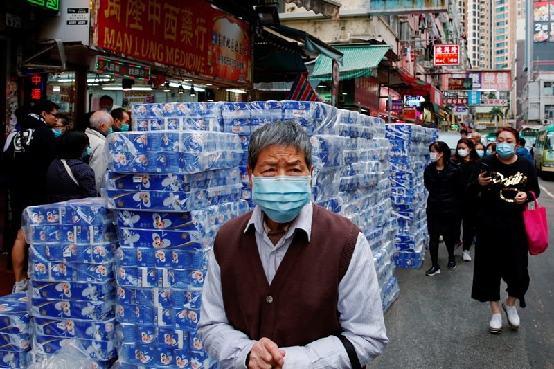 圖為香港民眾與身後成堆的衛生紙。 圖/路透社