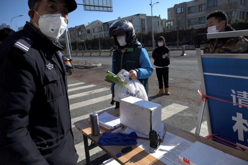 中國大陸北京一處住宅小區,警衛戴著口罩嚴格管制人員出入,一旁的民眾均人口一罩。  路透