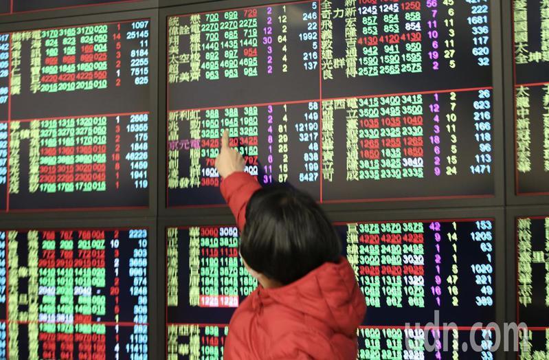台股一早開盤便呈現上下震盪,投資人在看盤螢幕前,指著個股表現與其他投資人進行討論。記者許正宏/攝影