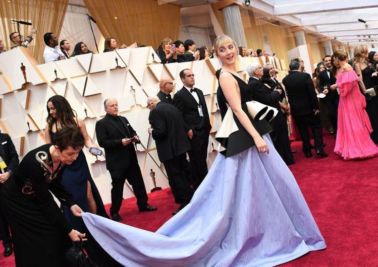 瑟夏羅南的GUCCI禮服以黑白立體飾裙配粉藍色長裙,打造高調的層次美。(法新社)