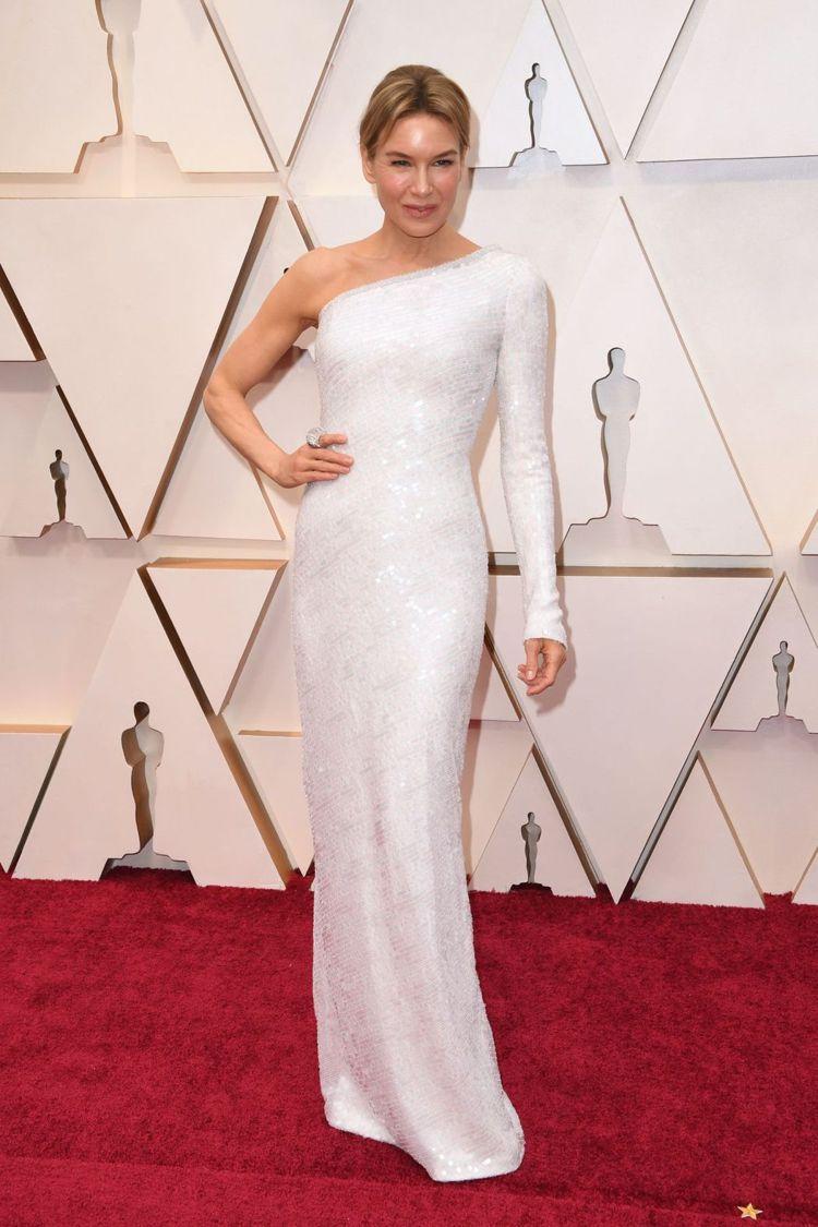 芮妮齊薇格的Armani露單肩不對稱長袖訂製服以貼身設計展現身材曲線,亮片堆疊的...