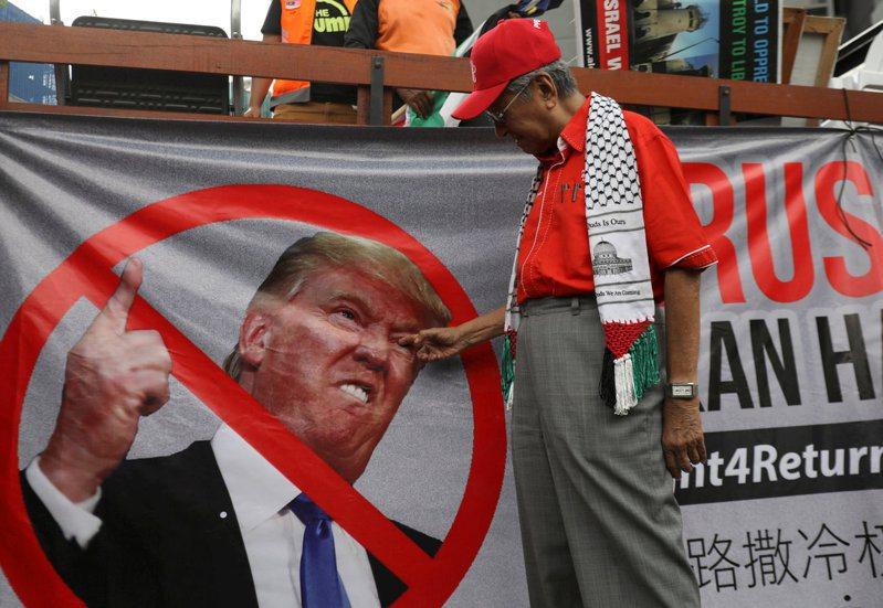 圖為2017年馬哈迪在一場抗議美國、支持巴勒斯坦活動上,朝反川普布條上的川普人像用手進行比劃的畫面。路透