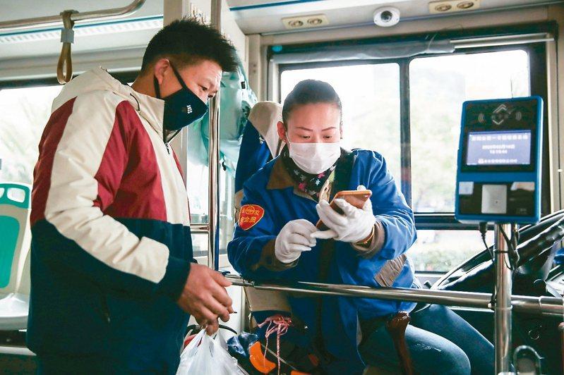 貴州貴陽昨實施防疫期間個人坐公交、地鐵、出租車等實名登記措施。圖為司機指導乘客實名登記。 中新社