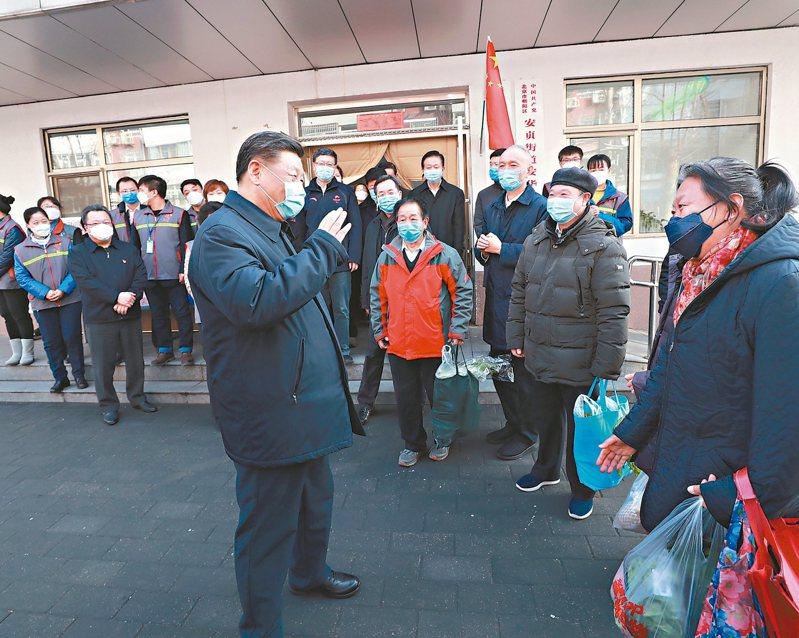 中共總書記習近平昨首度到基層視察新冠肺炎疫情防控,他全程戴著口罩與北京市民打招呼。 (新華社)