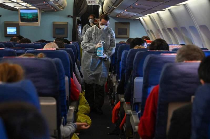 法國首班從武漢撤僑的專機1日飛行途中,機組人員拿著消毒液來回走動消毒。 (法新社)