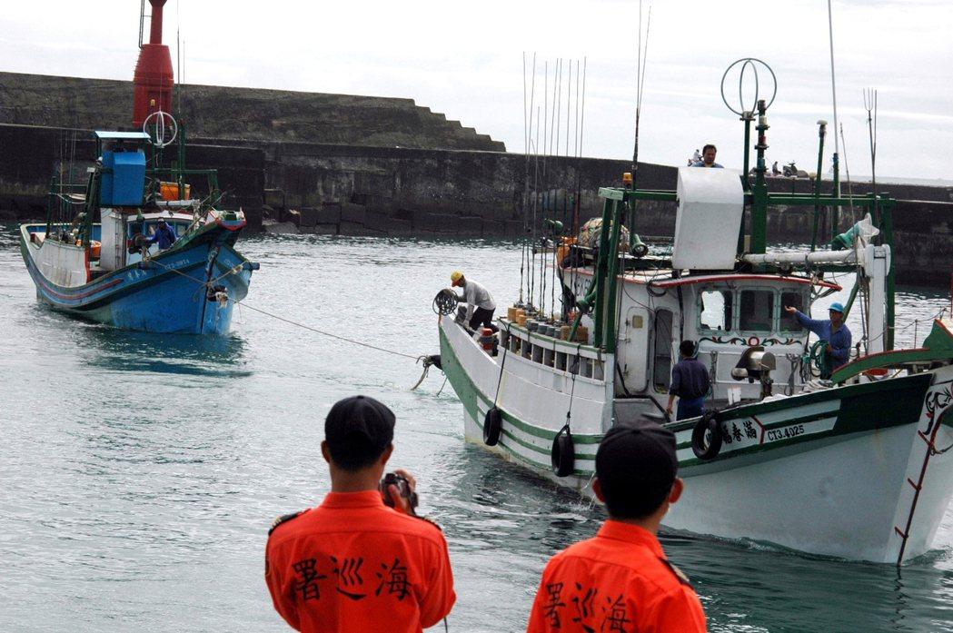 遭菲國軍方開槍掃射的滿春億號漁船(左),在海巡署巡邏艇戒謢下,由其他漁船拖回新港...