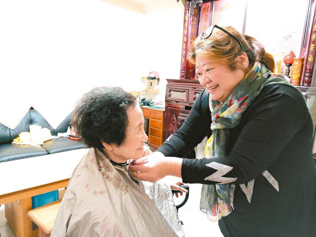 李春梅(右)從事過美髮業,經常熱心幫忙服務保戶,免費義剪。 記者戴永華/攝影