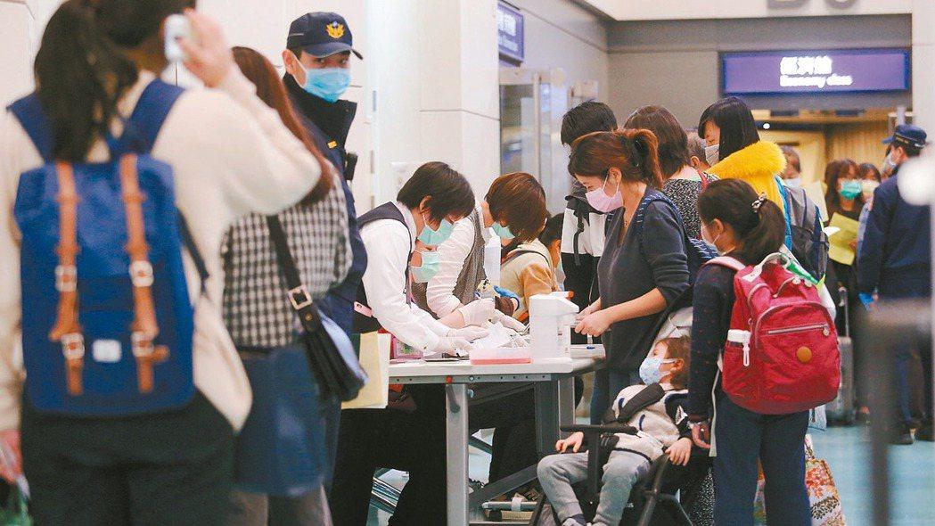 圖為抵桃園機場降落後旅客在空橋門口由疾管署檢疫官開立居家檢疫通知書。 記者陳嘉寧...
