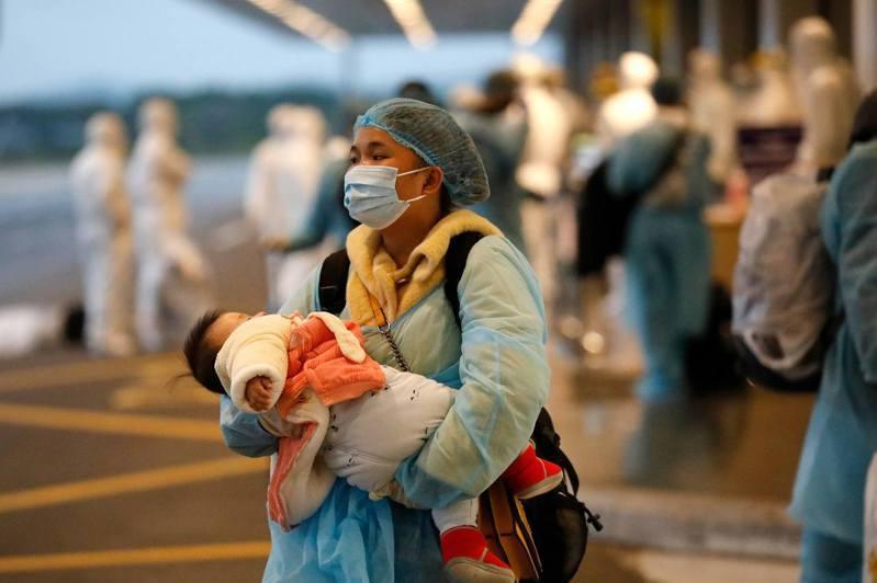 超級傳播者:武漢肺炎疫情已在多國出現,超級傳播者可能會使疫情更難控制。圖為2月10日一名由武漢回越南的婦女以及她手抱的孩子。(AFP)