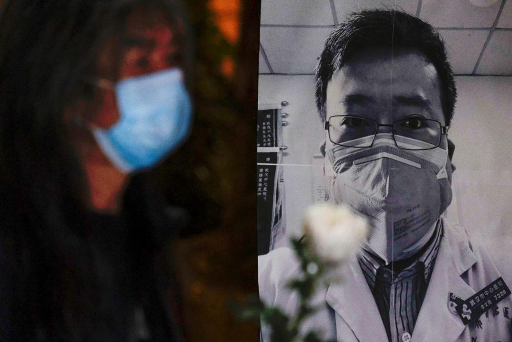 2月7日,一名香港民眾獻花悼念「吹哨人」李文亮醫師。 圖/路透社
