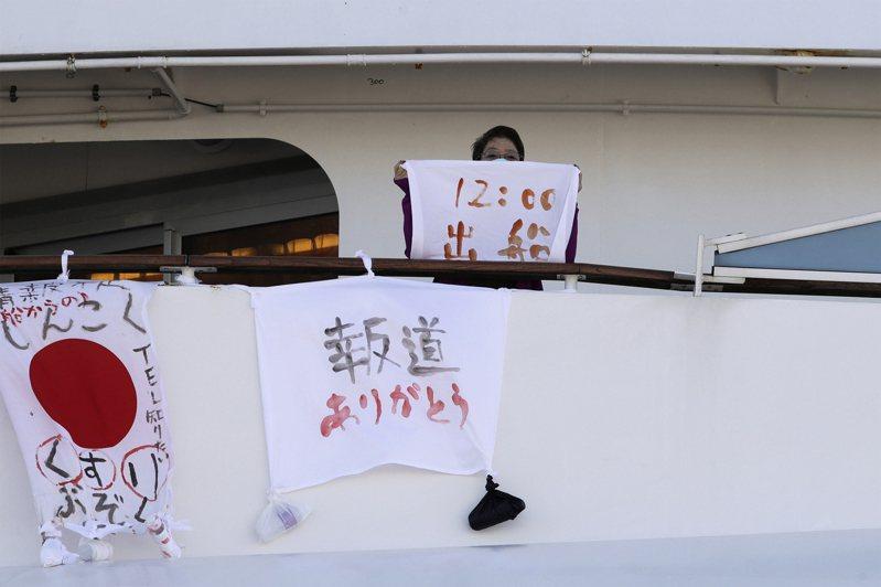 鑽石公主號郵輪上一名婦女手持布條,寫著出發時間,旁邊的標語上寫著「藥品短缺」、「感謝報導」字樣。美聯社