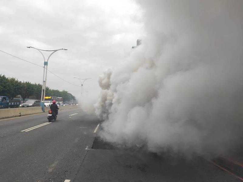 1輛工程吊車行經淡水馬偕醫院前方,突然猛烈冒煙,濃煙大到整個覆蓋車輛, 往來人車紛紛閃避。記者林昭彰/翻攝