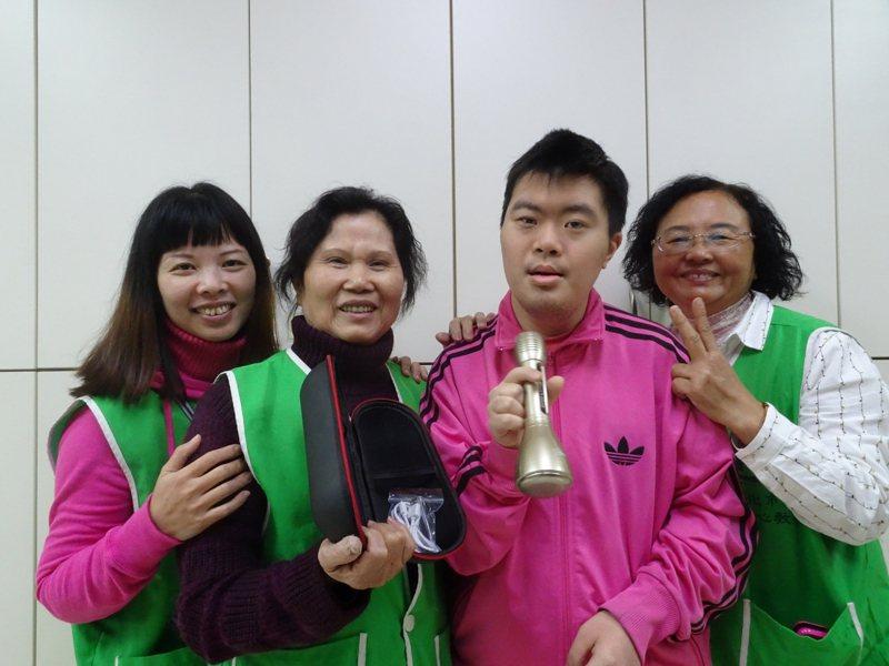 小曜(右二)收到志工隊送的藍芽無線麥克風,非常的開心的獻唱歌曲。圖/新北社會局提供