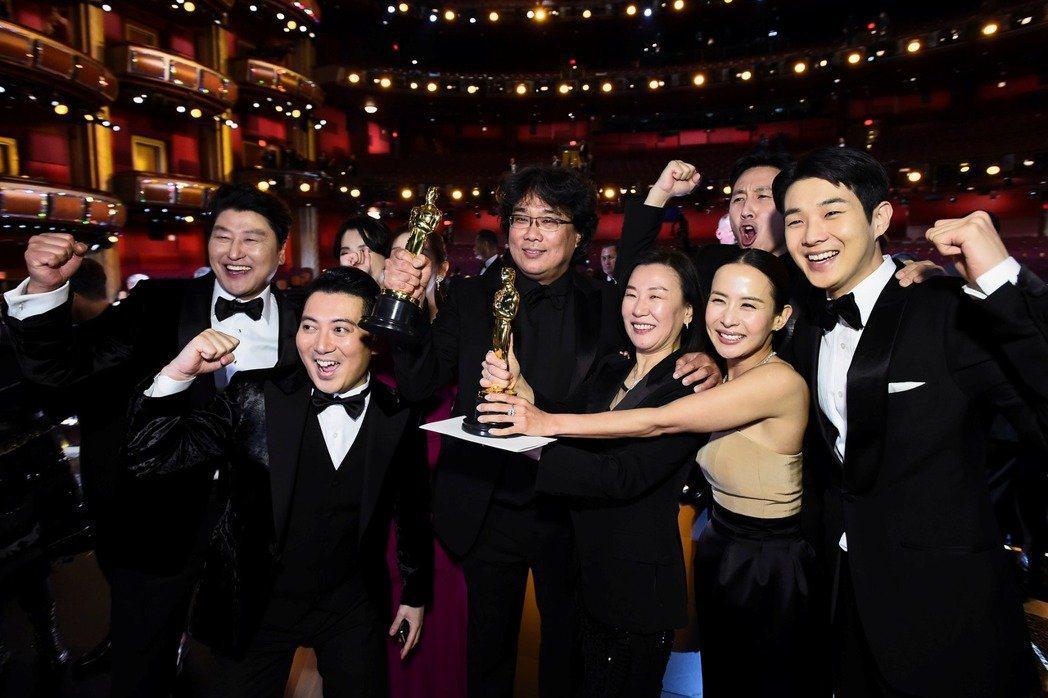「寄生上流」導演奉俊昊(中)與製片、主要演員因勇奪奧斯卡大獎留下勝利的笑容。圖/...