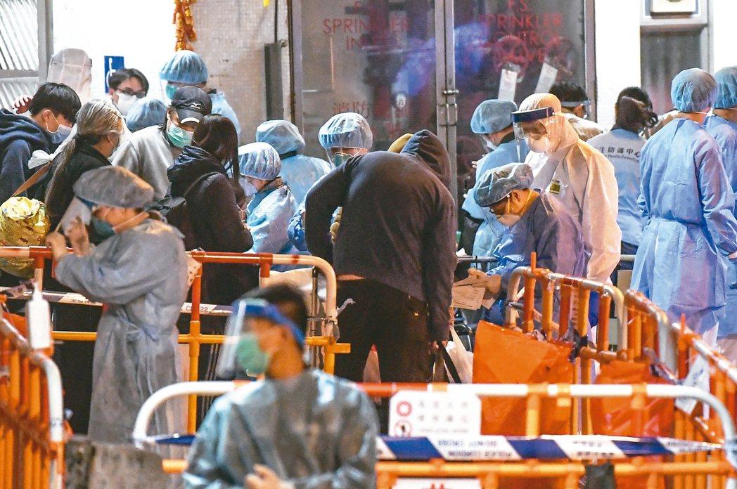 穿著防護衣的醫護人員及警員十一日在康美樓登記疏散居民。 (中通社)