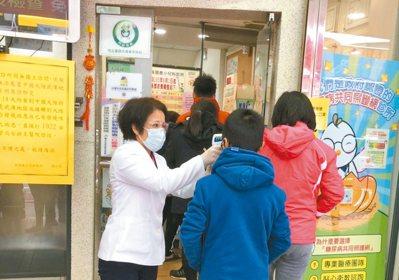 因應疫情,診所人員在門口幫民眾及陪同的家屬量體溫,才能進入看診。 圖/聯合報系資...