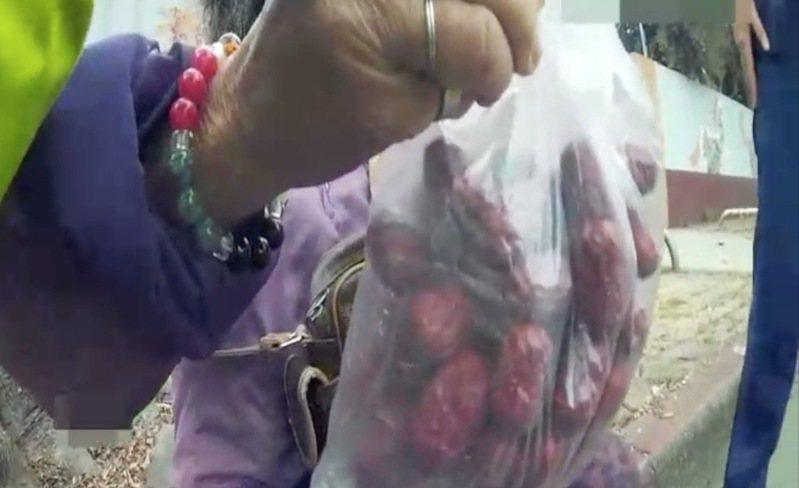 台中市大里區陳姓老嬤在9日騎車到東區樂成宮時,一時迷途警方前往協助,她拿出一包紅棗請警員吃,表達謝意。記者陳宏睿/翻攝